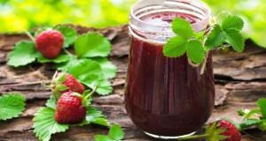 Ein Glas Erdbeerkonfitüre mit frischen Erdbeeren.