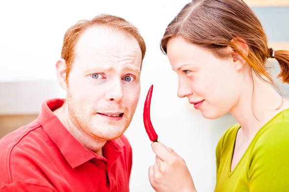 Junger Mann soll Chili essen, den ihm seine Frau anbietet.