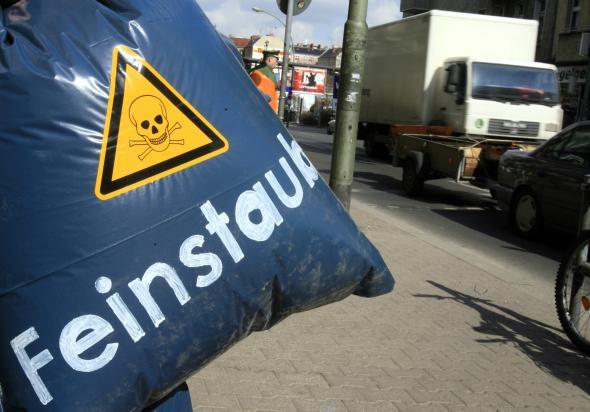 """BUND Demo - Plastikbeutel mit Gefahrenschild und der Aufschrift """"Feinstaub""""."""