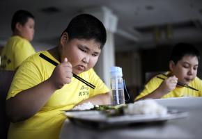 Übergewichtiger chinesischer Junge beim Mittagessen