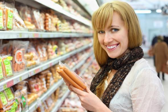 Junge Frau im Supermarkt - in der Hand hält sie ein Packung Würstchen