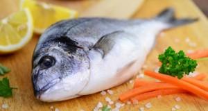 Frischer Fisch auf einem Küchenbrett.