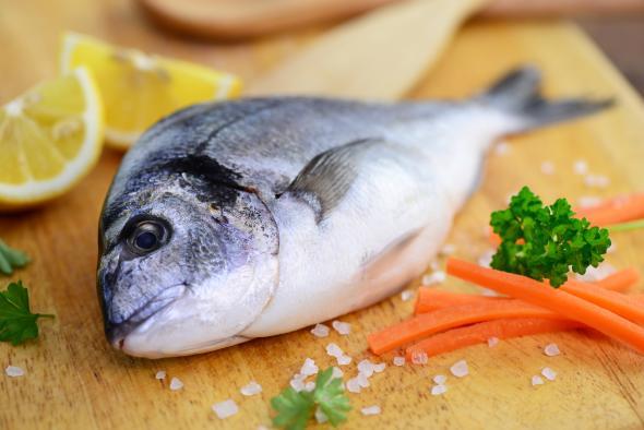 Frischer Fisch auf einem Küchenbrett: Gesunde Ernährung mit Omega-3-Fettsäuren.