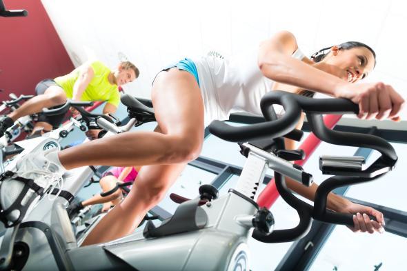 Junge Frau trainiert in einem Fitnessstudio und hat viel Freude am Spinning.