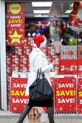 Frau mit Nikolausmütze läuft an einem Geschäft zur Weihnachtszeit vorbei