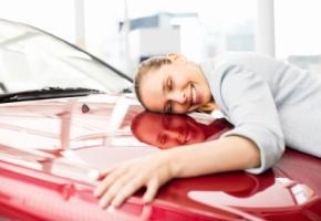 Junge Frau umarmt ihr neu gekauftes Auto