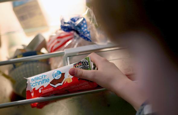 Ein Kind nimmt eine Milchschnitte aus dem Kühlschrank.