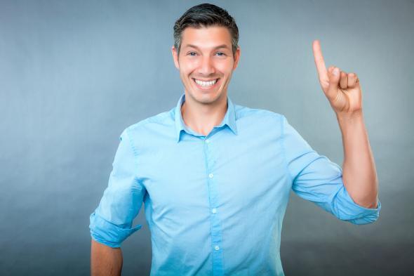 Ein Mann, freudestrahlend, zeigt mit dem Finger nach oben.