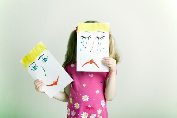 Kleines Mädchen hält Bilder mit unterschiedlichen Emotionen in ihren Händen.