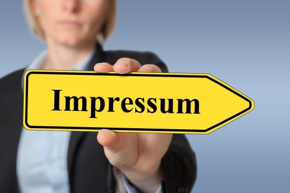 """Eine Frau hält ein Schild mit der Aufschrift: """"Impressum""""."""