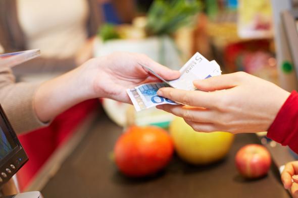 Eine Frau bezahlt ihre eingekauften Lebensmittel im Supermarkt mit Banknoten.