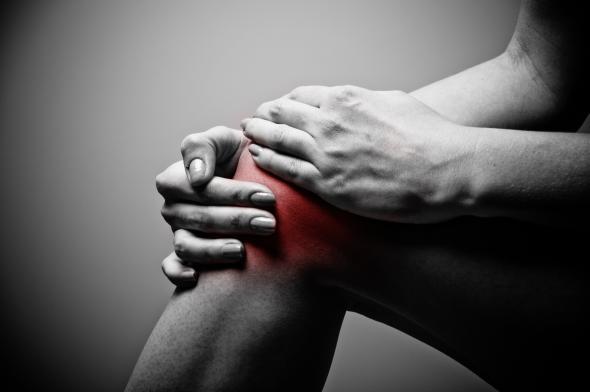 Schmerzen: Ein Mann hält sich sein Knie, das Knie ist rot makiert.