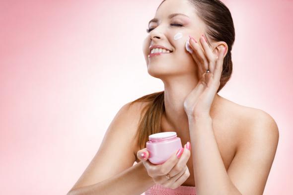 Eine junge Frau benutzt eine Gesichtscreme zur Pflege der Haut.