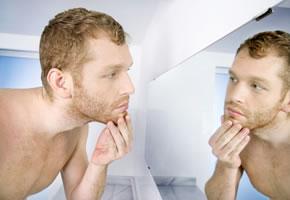 Mann vor dem Badezimmerspiegel