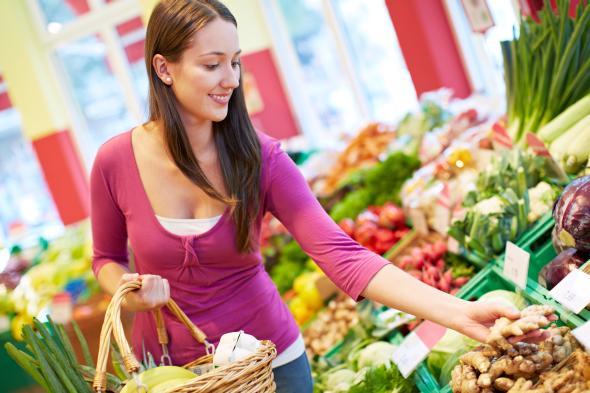 Junge Frau nimmt sich Ingwer aus dem Gemüseregal.