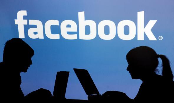 Junge und Mädchen sitzen am Laptop unter dem Facebook Schriftzug