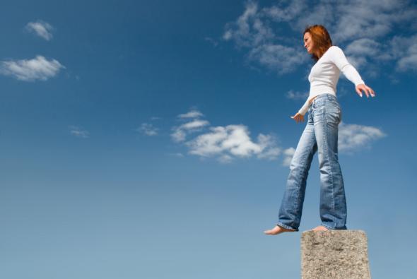 Eine Frau balanciert auf einem Stein.