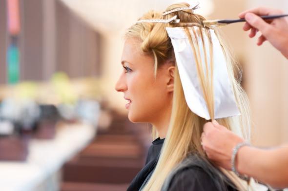 Junge Frau sitzt beim Frisör und lässt sich Strähnchen machen.