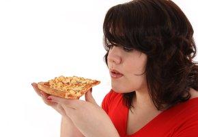 Heißhungerattacken: Die Frau isst ein Stück Pizza
