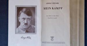 """Aufgeschlagene Seite von dem Buch """"Mein Kampf"""" mit einem Porträt von Adolf Hitler."""
