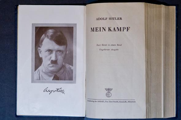 """Aufgeschlagene Seite von dem Buch """"Mein Kampf"""" - mit einem Porträt von Adolf Hitler."""