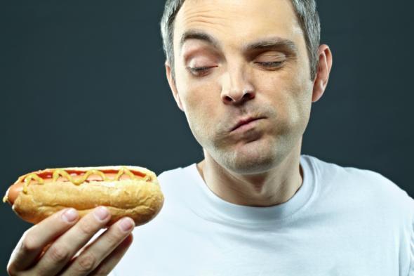 Mann beäugt einen Hot Dog