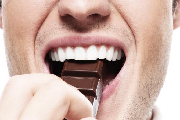 Mann beißt in ein Stück Zartbitterschokolade