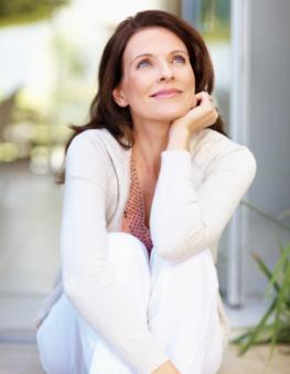 Eine Frau mittleren Alters sitzt nachdenklich auf einer Treppe