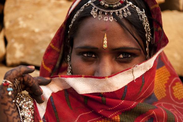 Junge indische Frau verschleiert ihr Gesicht.