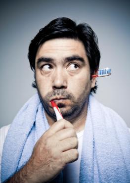 Mann putzt sich die Zähne, während aus dem linken Ohr die Zahnbürste herausschaut