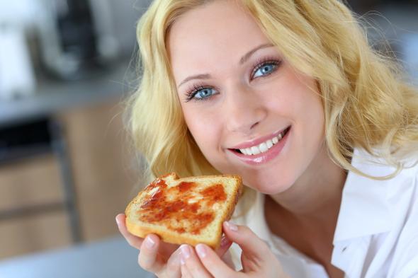 Jenny Craig Diät - Junge Frau isst ein Toastbrot mit Marmelade.