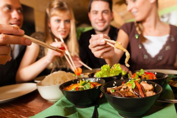 Eine Gruppe von Menschen isst asiatische Spezialitäten an einem Tisch.