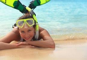 Junge Frau am Strand mit Taucherbrille und Schnorchel
