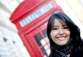 Junge Frau in London vor einer Telefonzelle