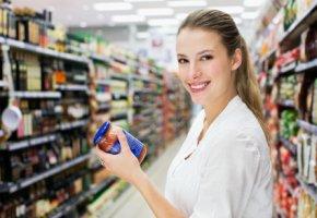 Junge Frau liest das Etikett von einer Tomatensauce im Supermarkt