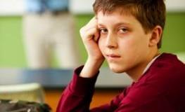 Schüler sitzt müde und abgespannt in der Klasse - der Lehrer ist im Hintergrund zu sehen