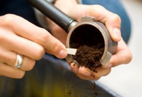 Kaffeesatz wird aus einem Portafilter entfernt