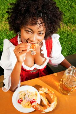 Junge Frau isst bayerische Spezialitäten auf dem Oktoberfest