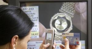 Junge Frau bestellt per Handy und Scheckkarte beim Homeshopping Sender