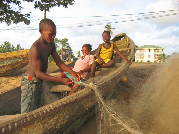 Kinder sitzen in einem Boot, ein Junge zeigt ein Fischernetz.