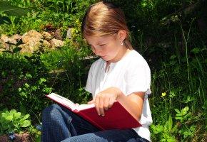 Kinderliteratur: Ein Mädchen liest ein Buch von Astrid Lindgren