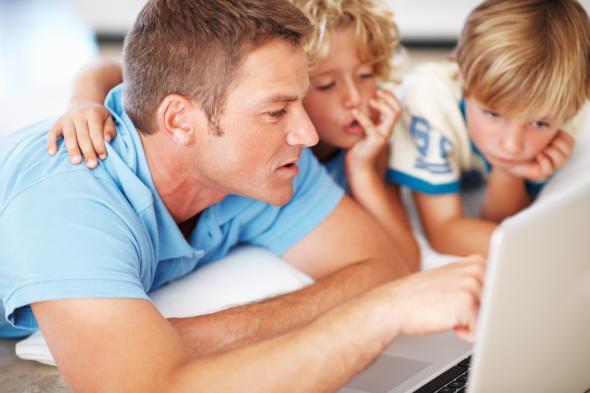 Ein Vater und seine Söhne sitzen vor einem Laptop und surfen.