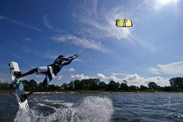 Ein Kiter wird von seinem Drachen aus dem Wasser gehoben.
