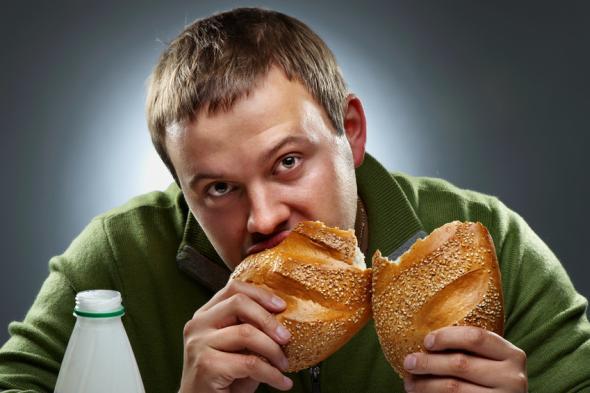 Ein Mann isst einen Laib Brot zum Abendessen.