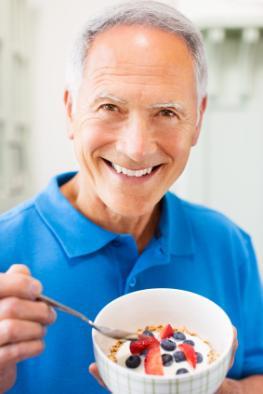 Senior mit einer Schüssel Müsli und Früchten