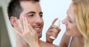 Eine Frau macht ihrem Mann eine Pflegecreme unter die Augen.