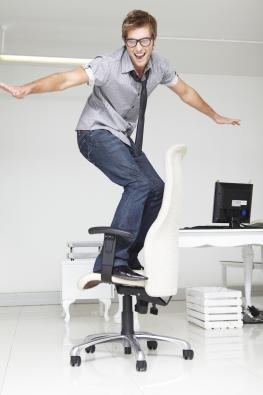 Junger Mann benutzt einen Bürostuhl als Skateboard