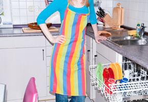 Eine Hausfrau räumt Ihre Geschirrspülmaschine aus