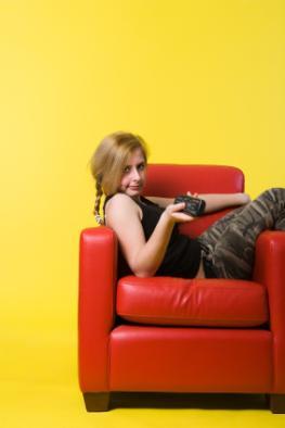 Teenager sitzt gelangweilt in einem Sessel und schaut fernsehen