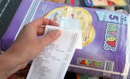 Kunde überprüft seinen Kassenzettel nach dem Einkauf im Supermarkt
